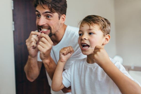 father and son flossing teetch
